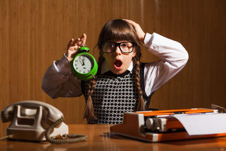 five to twelve: Shocked little girl holding clock that shows five to twelve time
