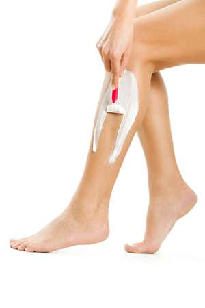 piernas mujer: Cierre de la imagen de la mujer que está afeitando sus piernas, aislado en blanco.