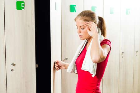 La muchacha cansada en el vestuario después del entrenamiento