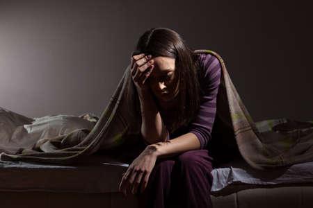 若い女性は眠ることができません。彼女は彼女のベッドに座っていると考えるです。