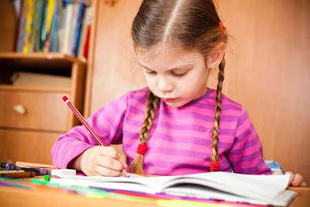 sketchbook: Preschooler child drawing in sketchbook at home.