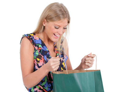 looking inside: Portrait of young woman who is looking inside shopping bag, isolated on white.