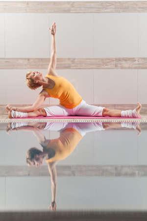 konasana: Young woman practicing yoga at swimming pool, Upavistha Konasana - Revolved Seated Angle Pose