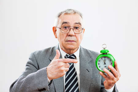 five to twelve: Senior businessman pointing at clock that shows five to twelve time
