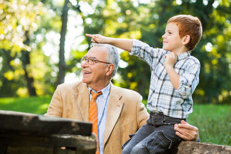 Grandfather and grandson sitting and talking in park