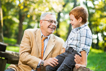 little man: Grandfather and grandson sitting and talking in park