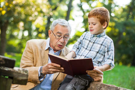 Grandfather and grandson reading book and learning about nature