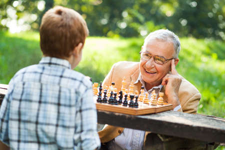 Grandfather and grandson are playing chess in park Stock Photo
