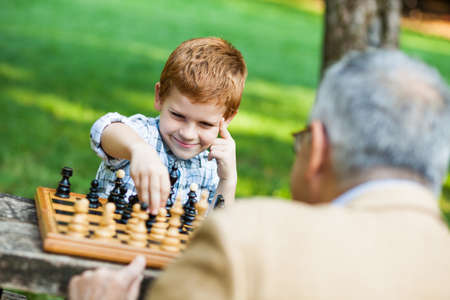 Grandfather and grandson are playing chess in park Foto de archivo