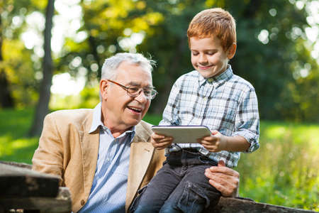 two people: Grandfather and grandson are using digital tablet in park