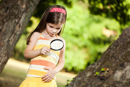 exploring: Little girl exploring nature with loupe in park