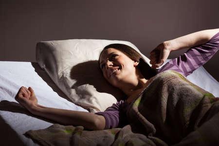 Giovane donna svegliarsi al mattino presto. E 'ora di alzarsi per il lavoro.