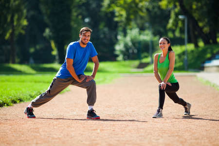 Young couple stretching their bodies, warming up for jogging