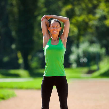 warming up: Young woman stretching her body, warming up for jogging