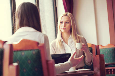 Two young women sitting in cafe and talking, intentionally toned image.