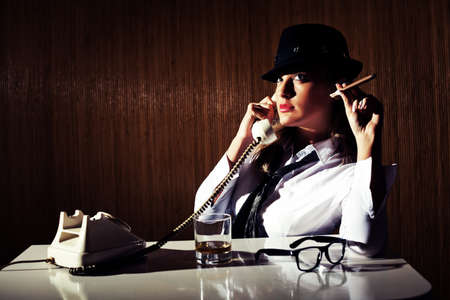 liquor girl: Retro styled businesswoman smoking cigar and talking on telephone. Image is intentionally toned. Stock Photo