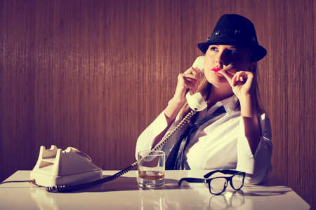 Retro styled businesswoman smoking cigar and talking on telephone. Image is intentionally toned. Stock Photo