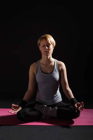 lotus position: Young woman practicing yoga, Padmasana  Lotus Position Stock Photo