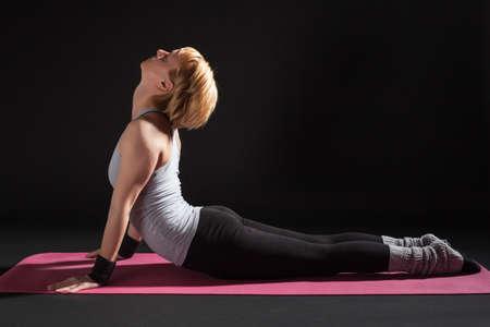 bhujangasana: Young woman practicing yoga, Bhujangasana  Cobra Pose