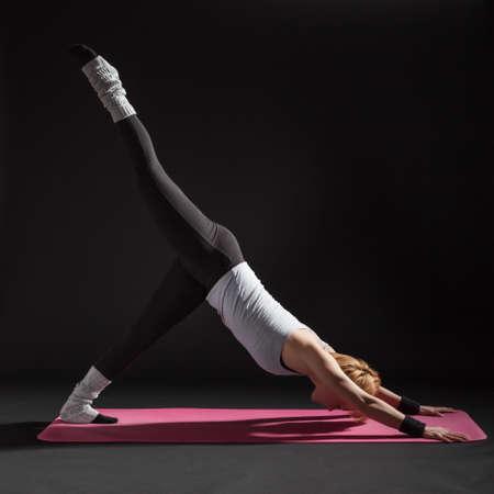 eka: Young woman practicing yoga, Eka Pada Adho Mukha Svanasana  One-Legged Downward-Facing Dog Pose
