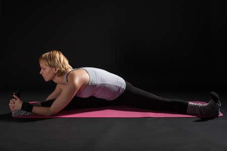 konasana: Young woman practicing yoga, variation of Upavistha Konasana  Seated Angle Pose
