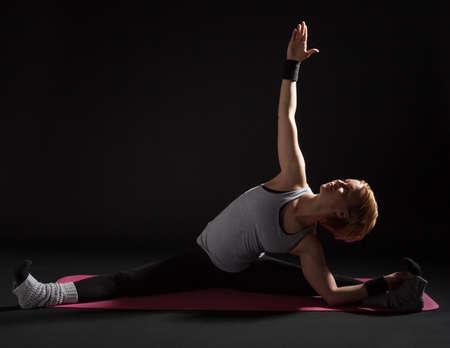 konasana: Young woman practicing yoga, Upavistha Konasana  Revolved Seated Angle Pose
