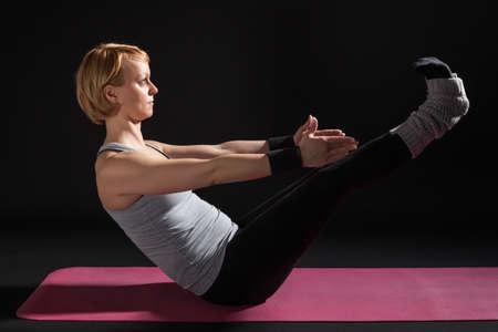practicing: Young woman practicing yoga, Navasana  Boat position