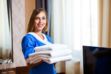 Happy hotel maid is holding towels in hotel room