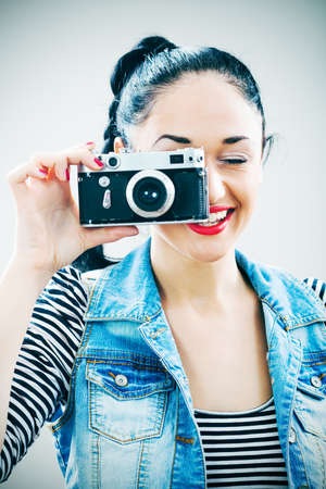 intentionally: Portrait of happy girl with retro photo camera, intentionally toned.