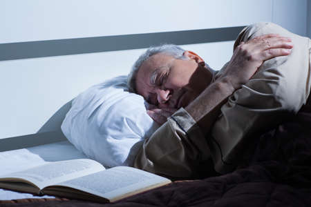 Senior man fell asleep in his bed after reading book.