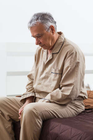sullen: Worried senior is waking up. He is sitting on bed ready to get up. Stock Photo