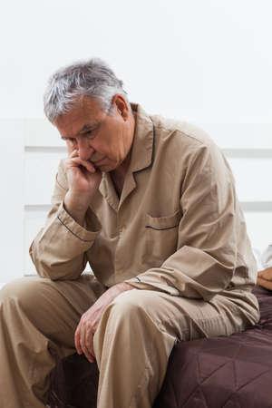 awake: Worried senior man can not sleep. He is sitting on his bed.