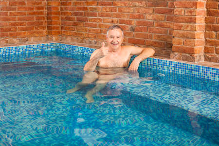 hydromassage: Happy senior man is relaxing in hydromassage pool.