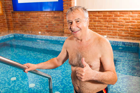 the entering: Happy senior man is entering hydromassage pool. Stock Photo