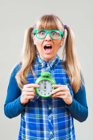 five to twelve: Studio shot portrait of nerdy woman who is holding clock that shows five to twelve time Stock Photo