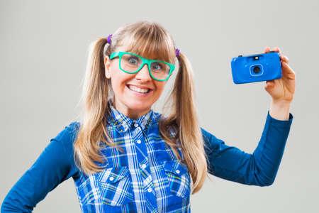 nerdy: Studio shot portrait of happy nerdy woman who is holding photo camera