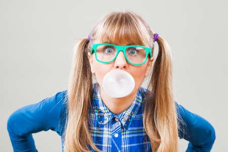 bubble gum: Studio shot portrait of nerdy woman who is blowing bubble gum.