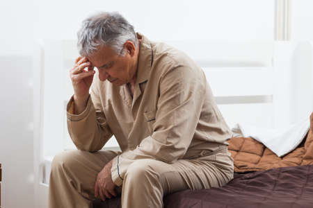 Worried senior man can not sleep. He is sitting on his bed with headache. Foto de archivo