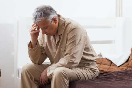 Preoccupato uomo anziano non riesce a dormire. Si è seduto sul letto con mal di testa.