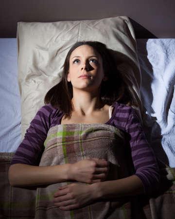 despertar: Joven no puede dormir. Ella está tumbado en su cama y pensando.