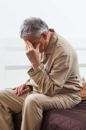 心配している年配の男性は眠ることができません。彼は頭痛と彼のベッドの上に座っています。 写真素材