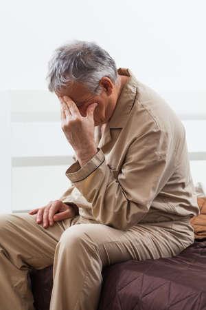 senior man Worried ne peut pas dormir. Il est assis sur son lit avec des maux de tête.