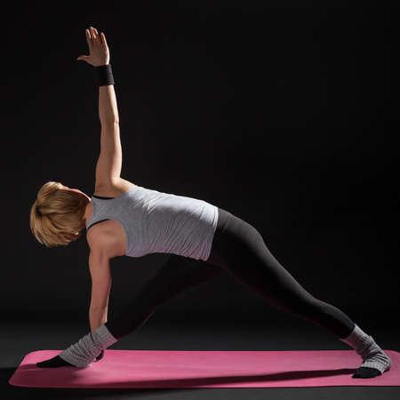 trikonasana: Young woman practicing yoga, Trikonasana  Bikram triangle left