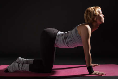 practicing: Young woman practicing yoga, Marjaryasana  Cat Pose