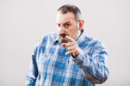 expressing negativity: Studio shot portrait of angry man pointing at someone