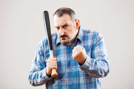 threatens: Portrait of angry man with baseball bat who threatens