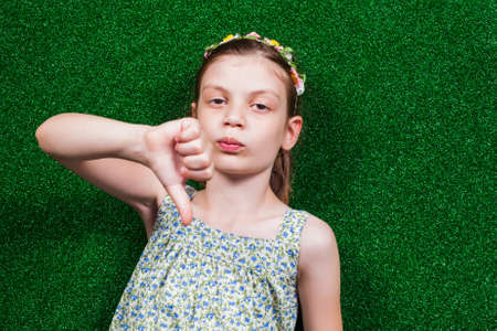 handsign: Little girl is lying on artificial grass and showing thumb down.