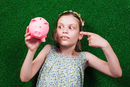 handsign: Little girl is lying on artificial grass and pointing at her piggy bank