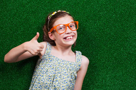handsign: Happy little girl is lying on artificial grass and showing thumb up. Stock Photo