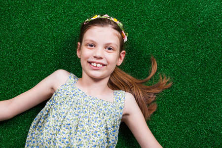 handsign: Happy little girl is lying on artificial grass.